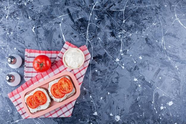 Pokrojone pomidory na chleb serowy obok soli na ręczniku, na niebiesko.