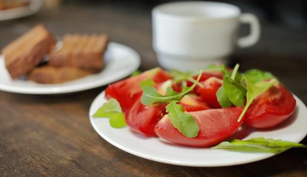 Pokrojone pomidory z sałatą na białym talerzu i chleb