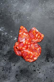 Pokrojone salami chorizo. hiszpańska tradycyjna kiełbasa chorizo. czarne tło. widok z góry