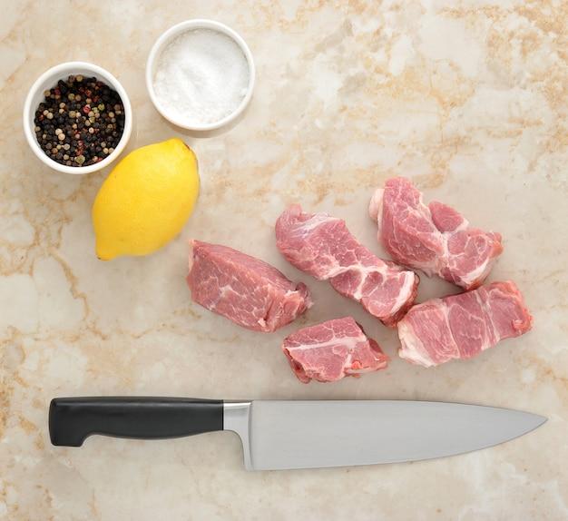 Pokrojone surowe mięso wieprzowe oraz sól i pieprz na marmurze