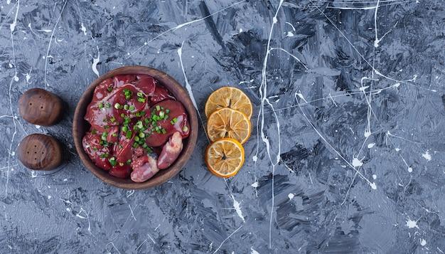 Pokrojone suszone cytryny i podroby w misce, na niebieskim stole.