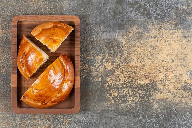 Pokrojone świeże ciasto na drewnianym talerzu.