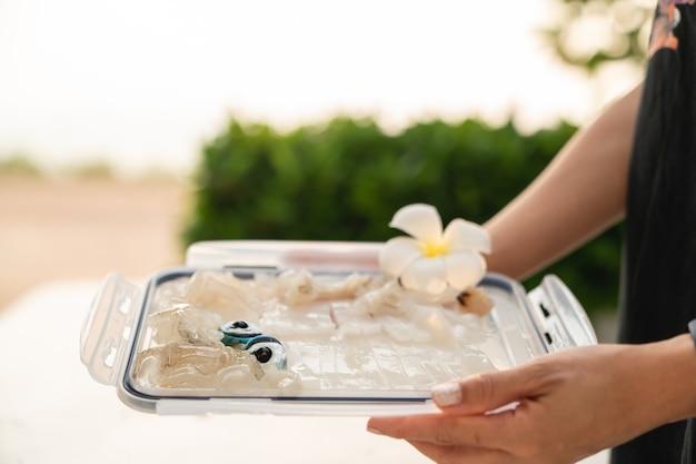 Pokrojone świeże surowe sashimi z kałamarnicy, podawane w plastikowej tacy.