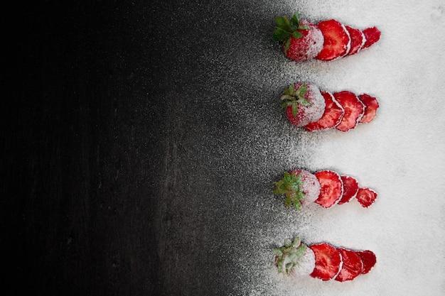Pokrojone świeże truskawki sproszkowany cukier na czarno. widok z góry, ramka. copyspace. letnia rama z owocami.