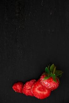 Pokrojone truskawki z liśćmi na czerni. widok z góry, ramka. copyspace. letnia rama z owocami.