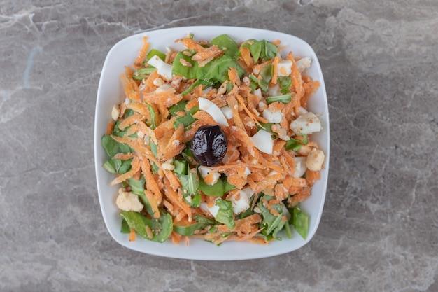 Pokrojone w kostkę marchewki i sałatka jarzynowa w białej misce.