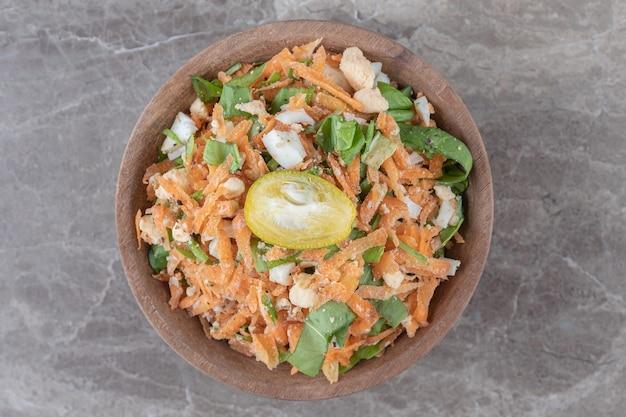 Pokrojone w kostkę marchewki i sałatka jarzynowa w drewnianej misce.