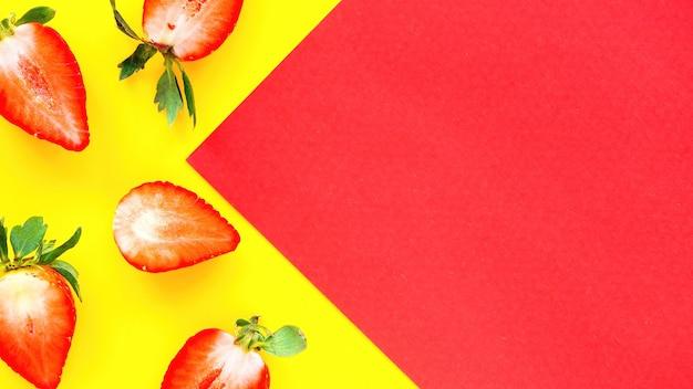 Pokrojone w pół truskawki i czerwony papier na żółtym tle