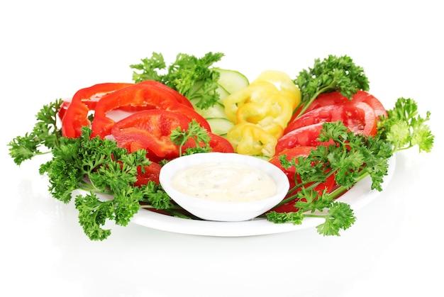 Pokrojone warzywa i sos na talerzu na białym