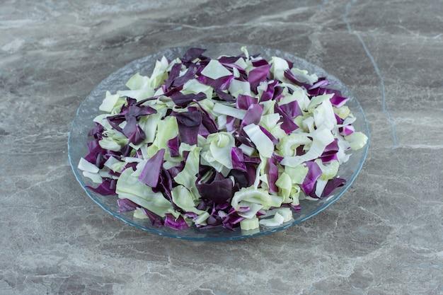 Pokrojone warzywa w szklanej misce, na marmurowym stole.