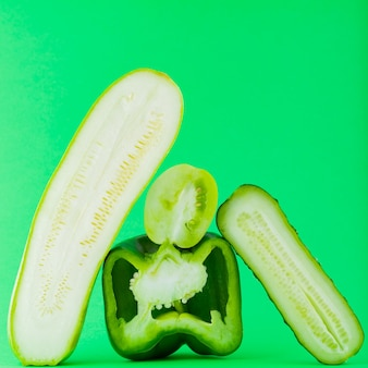 Pokrojone zielone warzywa na zielonej ścianie. papryka, pomidor, ogórek i cukinia dla wegan. koncepcja zdrowej żywności. spadające warzywa