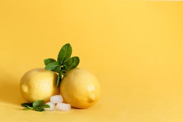 Pokrojone żółte cytryny na brązowej drewnianej desce, obok niej leży wiązka zielonej mięty