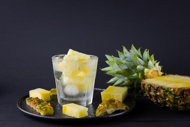 Pokrojony ananas na czarnym talerzu. pij z lodem i plasterkami ananasa. napełniona woda. copyspace