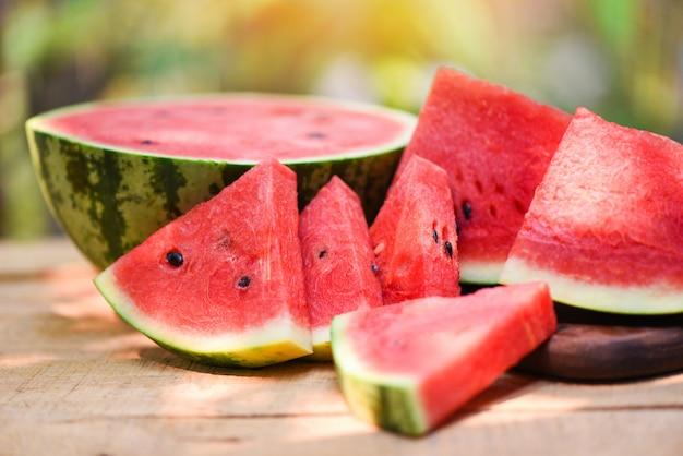 Pokrojony arbuz na drewnianym i naturze. zamyka w górę świeżego arbuza składa tropikalną lato owoc