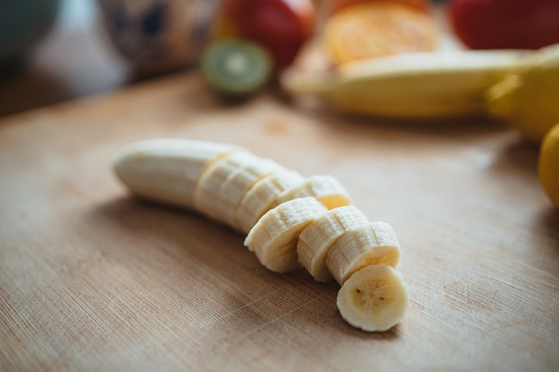 Pokrojony banan na drewnianym stole otoczony innymi owocami.