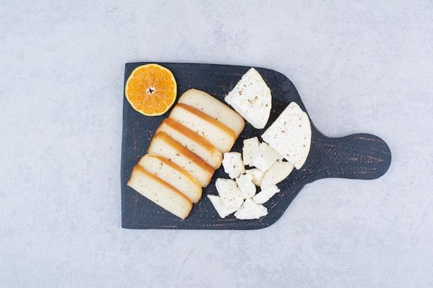 Pokrojony biały chleb z plasterkiem pomarańczy na desce do krojenia.