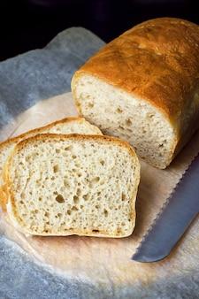Pokrojony bochenek domowego chleba na papierze do gotowania.