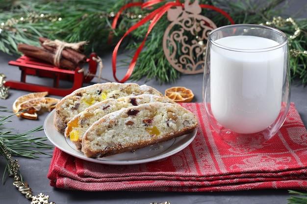 Pokrojony bożonarodzeniowy smaczny stollen z suszonymi owocami i szklanką mleka. uczta dla świętego mikołaja. tradycyjne niemieckie smakołyki. zbliżenie
