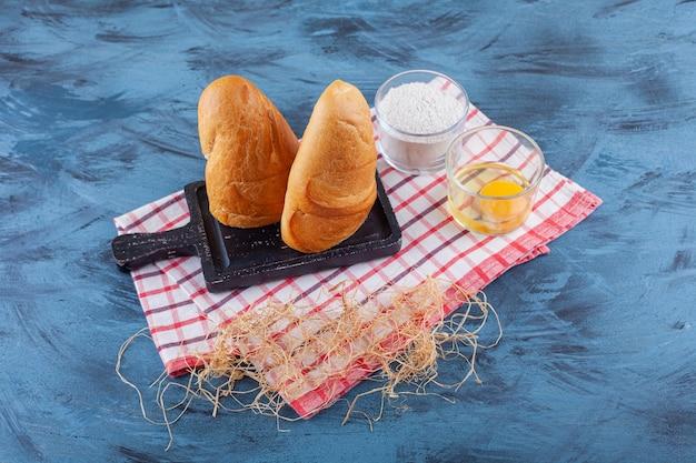 Pokrojony chleb na desce obok mąki i jajka na ściereczce, na niebieskiej powierzchni.