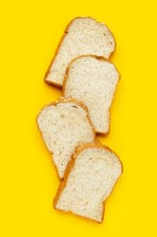 Pokrojony chleb pełnoziarnisty na żółtym tle.