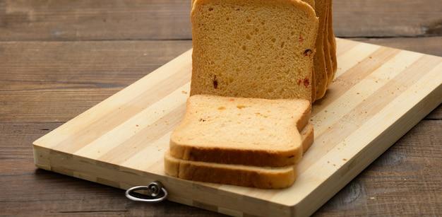 Pokrojony chleb z białej mąki pszennej na drewnianej desce. chleb kanapkowy