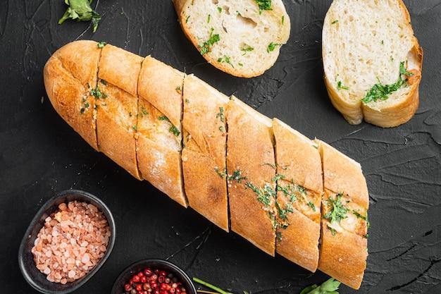 Pokrojony chleb z grilla z zestawem czosnku i ziół, na czarnym ciemnym tle kamiennego stołu, widok z góry płaski lay