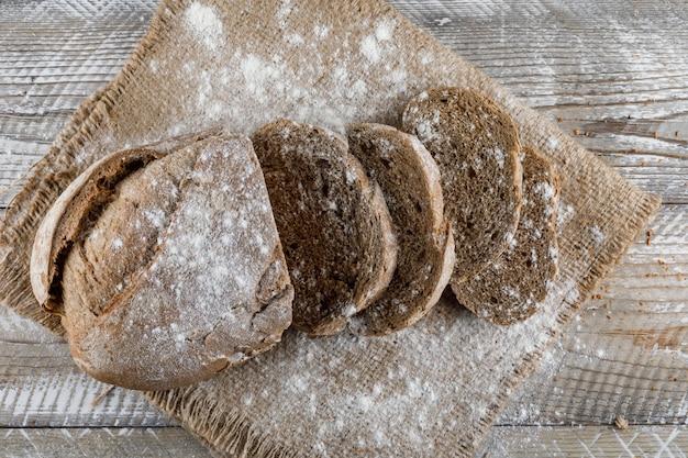 Pokrojony chleb z mącznym stołowym odgórnym widokiem na drewnianej powierzchni