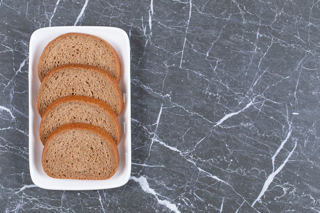 Pokrojony chleb żytni na białym talerzu na szaro.