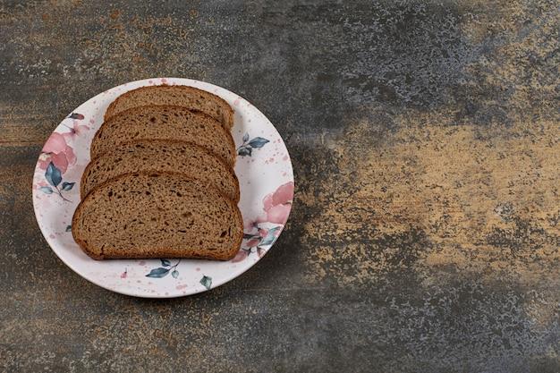Pokrojony chleb żytni na kolorowy talerz