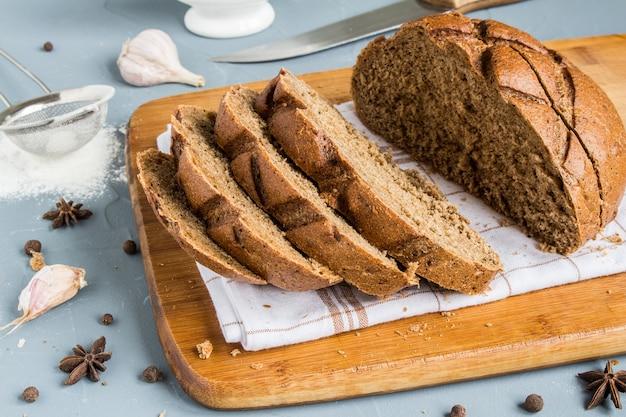 Pokrojony chleb żytni na ręczniku na stole z przyprawami