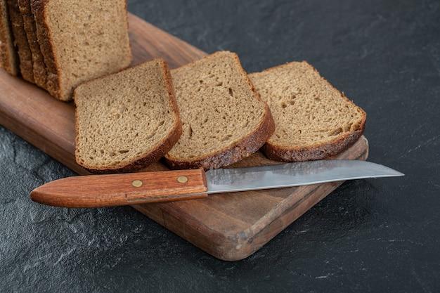 Pokrojony chleb żytni umieszczony na drewnianej desce do krojenia