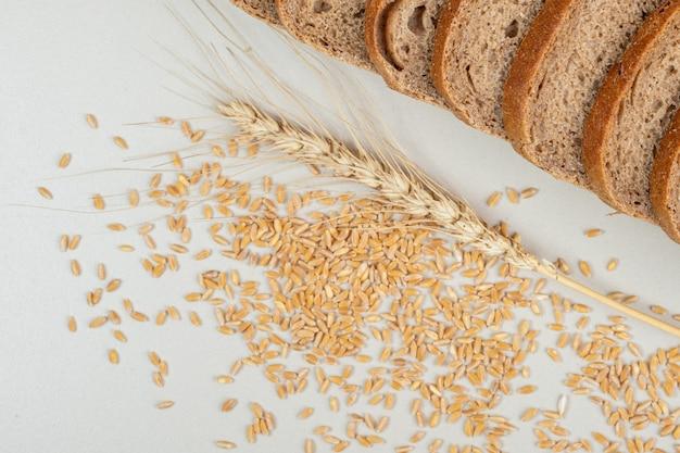 Pokrojony czarny chleb i kłos pszenicy na kamiennej powierzchni.