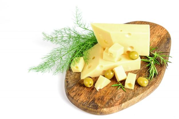 Pokrojony emmentalny ser z zielenią i oliwkami na desce do krojenia, przestrzeń
