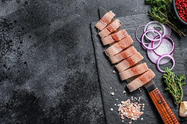 Pokrojony filet z marynowanego śledzia z cebulą i tymiankiem