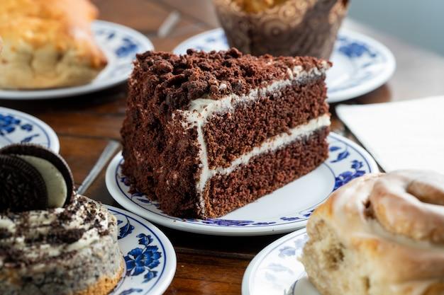 Pokrojony kawałek pysznego ciasta czekoladowego na niebiesko-białym talerzu otoczony innymi słodyczami