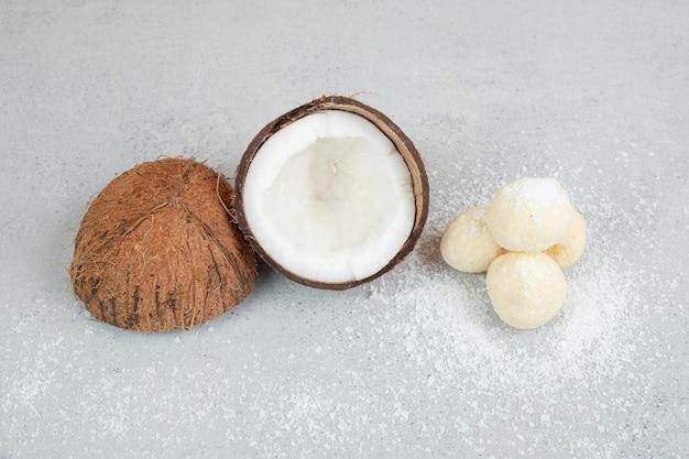 Pokrojony kokos z okrągłymi słodkimi ciasteczkami na białej powierzchni.
