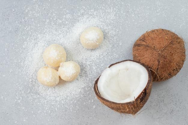 Pokrojony kokos z okrągłymi słodkimi ciasteczkami na białej powierzchni