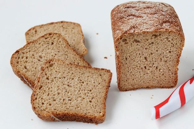 Pokrojony kwadratowy chleb z mąki pełnoziarnistej, znajdujący się na białym tle, zbliżenie
