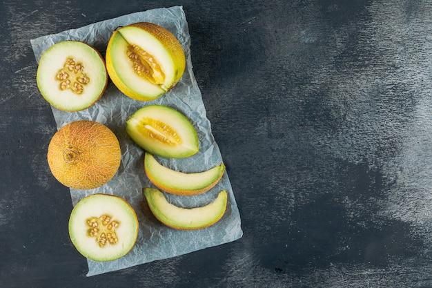 Pokrojony melon na ciemnym drewnianym i szarym sukiennym tle. widok z góry. miejsce na tekst