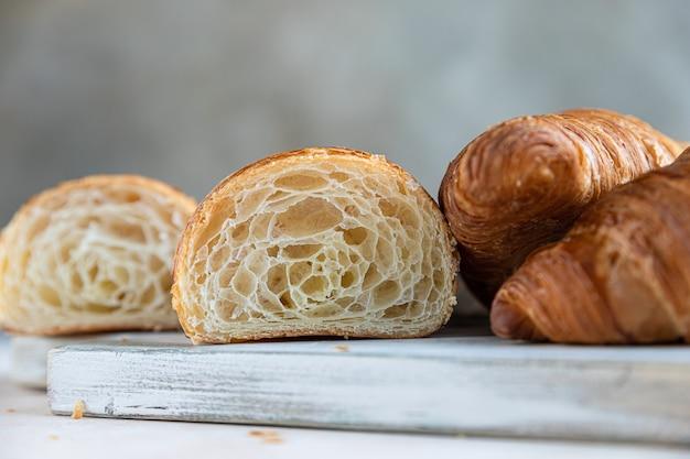 Pokrojony na pół rogalika o wewnętrznej teksturze i cienkich chrupiących warstwach pyszne ciasto francuskie