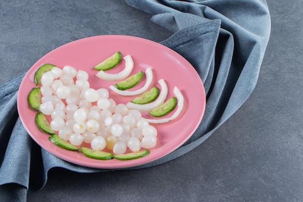 Pokrojony ogórek i piklowana cebulka na talerzu na kawałkach materiału, na marmurowej powierzchni.