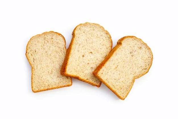 Pokrojony pełnoziarnisty chleb na białym tle.