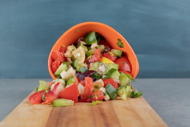 Pokrojony pomidor i ogórek sandałowy w filiżance z ziołami
