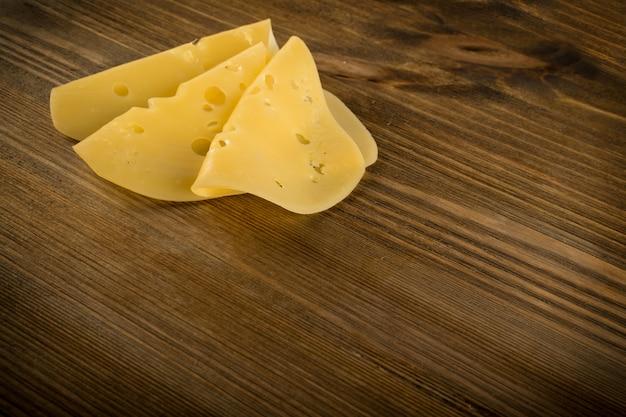 Pokrojony ser nad nieociosanym drewnianym tłem