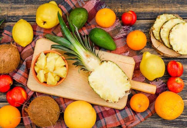 Pokrojony soczysty ananas w drewnianej desce i misce z bliska kokosy, brzoskwinie, pigwy i owoce cytrusowe na powierzchni drewna grunge i tkaniny piknikowej