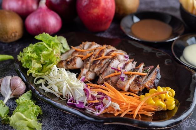 Pokrojony stek wieprzowy z chlebem, marchewką, kalafiorem, sałatą i kukurydzą na czarnym talerzu.