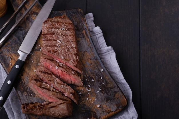 Pokrojony stek wołowy doprawiony solą na desce do krojenia oraz nożu i widelcu
