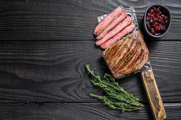 Pokrojony stek wołowy lub bavette na tasaku. czarne drewniane tło. widok z góry. skopiuj miejsce.