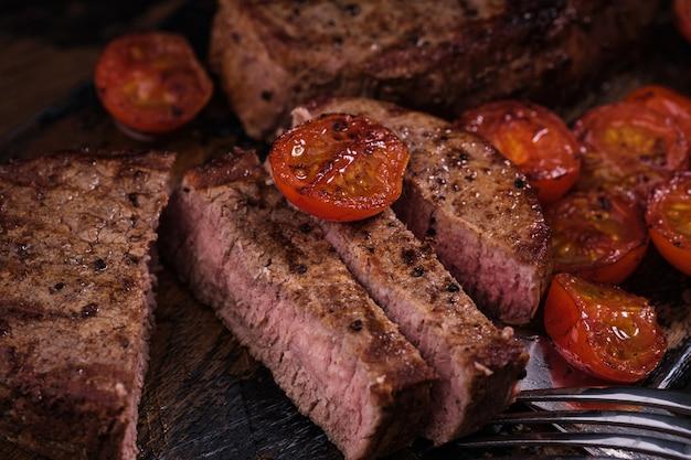 Pokrojony stek wołowy z pomidorem. mięso z grilla z bliska