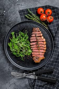 Pokrojony stek z polędwicy, marmurkowe mięso wołowe z rukolą. czarna powierzchnia. widok z góry